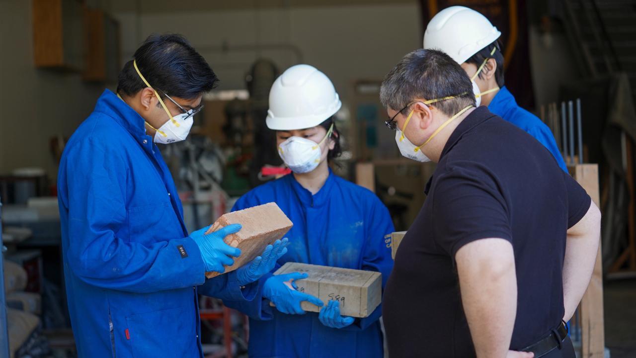 From left, Nitin Kumar, Julie Nguyen, Michele Barbato and Thomas Tonthat examine earth blocks the team has made and burned. (Karin Higgins/UC Davis photo)
